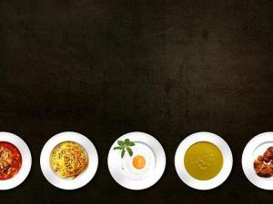 fünf verschiedene Gerichte auf weißen Tellern